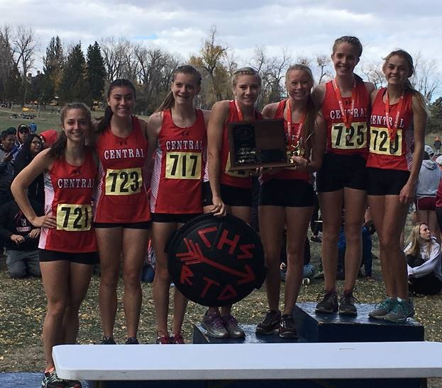 Members of the girls' cross country team stand on the podium with their state champions trophy.  L-R Jenna Goodrich, junior,